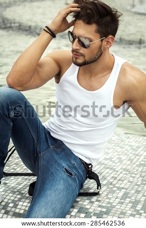 Sexy man in aviator sunglasses touching his hair - stock photo