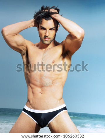Sexy man posing against summer background - stock photo