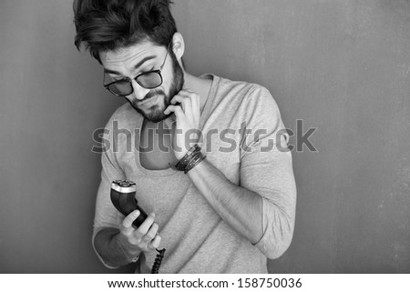 sexy man rubbing his beard holding a shaving machine against wall - stock photo