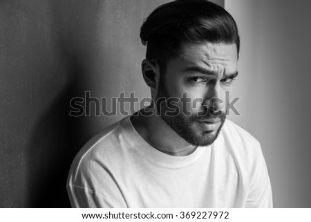 sexy man with beard looking dramatic portrait against wall