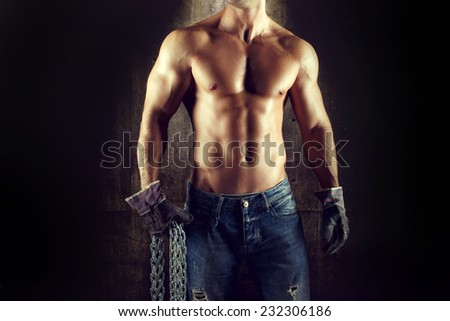 Sexy man worker body, in jeans and gloves with chain - stock photo