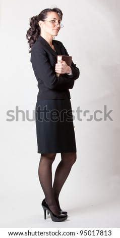Sexy mature woman holding a book in studio - stock photo