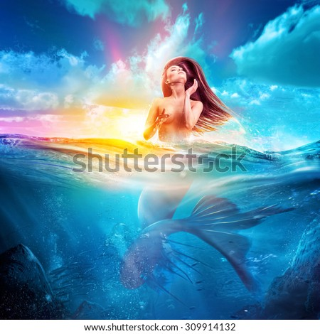 sexy mermaid emerges out from sea at sunset. concept art - stock photo