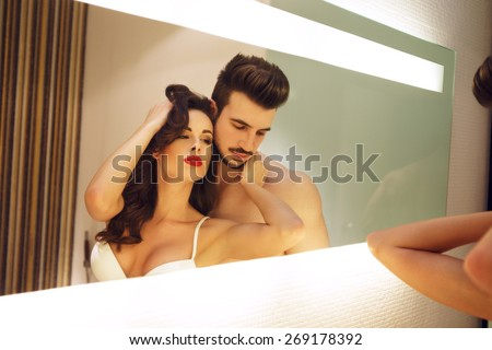 Sexy milf with young breaded lover posing in mirror - stock photo
