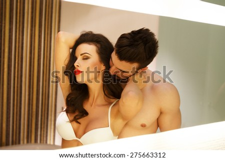 Sexy milf woman with young macho lover posing in mirror - stock photo