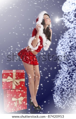 Sexy model in a red christmas dress with short skirt and hood with white fur and 2 big gift boxes kissing a snowman - stock photo