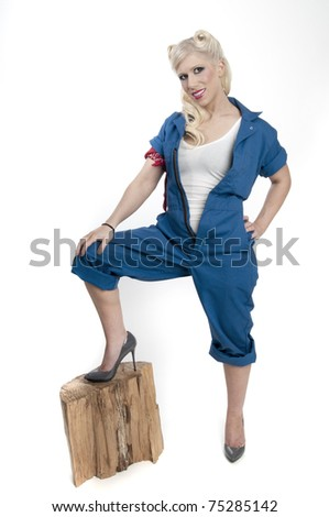 Sexy model in coveralls with foot on a stump - stock photo
