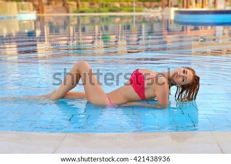 Sexy model wearing bikini in the pool - stock photo