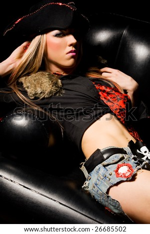 Sexy model wearing pirate outfit and red boots leaning on black leather sofa