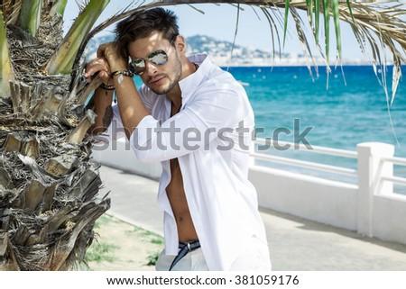 Sexy model wearing white shirt in aviator sunglasses - stock photo