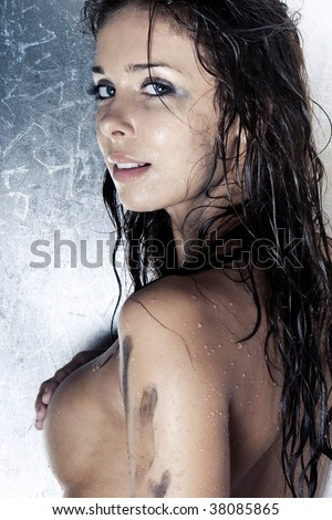 sexy model with wet and dirty skin and hair taking a shower - stock photo