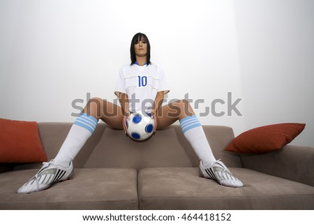 Sexy model woman holding a soccer ball in between her legs and sitting on a couch with two cushion pillows with the white wall background