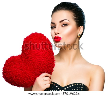 Sexy model Woman portrait. Gorgeous young brunette woman with heart shaped red pillow. Perfect make up. Kiss. Valentine' Day brunette lady headshot - stock photo