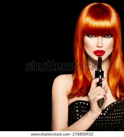 Sexy model woman with a gun. Beauty girl portrait, beautiful lady with revolver. Perfect long red hair, fringe hairstyle, red lips. Makeup. Isolated on Black background - stock photo