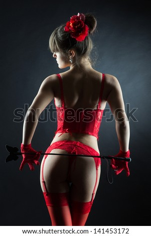 Sexy muscled woman in red lingerie holding leather stick with butterfly - stock photo