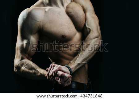 Sexy muscular male torso of athlete bodybuilder posing in power with veins on hands and bare chest on black background