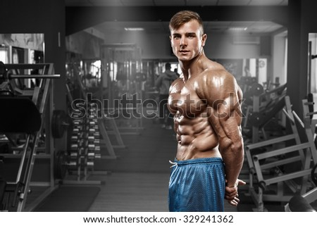 Sexy muscular man posing in gym, shaped abdominal, showing triceps. Strong male naked torso abs, working out - stock photo
