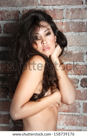 Sexy naked brunette posing on wall background