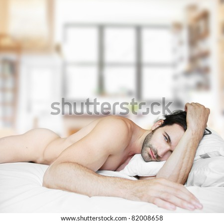 Sexy nude male model in bed at home alone - stock photo