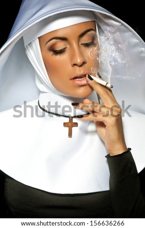 Sexy nun. Halloween. Nun smoking - stock photo