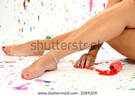 Sexy pair of legs in paint in paint splattered studio. - stock photo