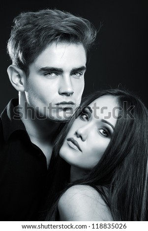 Sexy passion couple, beautiful young man and woman closeup, studio shot toned blue