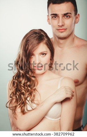 Sexy passionate couple in studio. Handsome half naked semi nude man and pretty woman in lingerie. Love and passion.