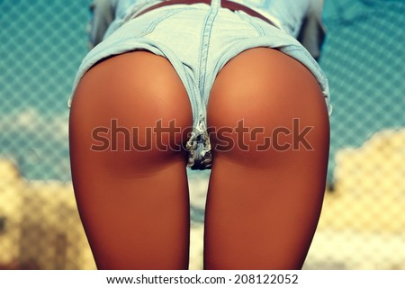 Sexy perfect female woman buttocks ass on blue sky city outdoors background in jeans shorts - stock photo