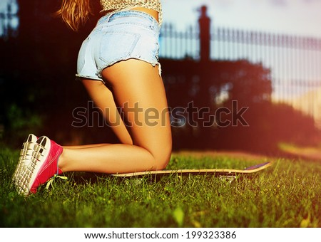 Sexy perfect girl woman buttocks on green grass summer background with skateboard in bright colorful running shoes in blue short jeans - stock photo