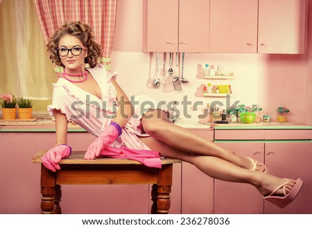 Sexy pin-up girl wearing pink bathrobe alluring on her pink kitchen at home. Fashion. Full length portrait. - stock photo