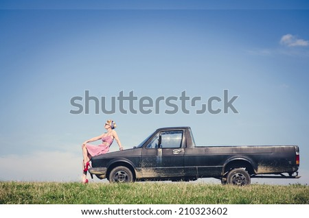 Sexy pin-up style girl sitting on the hood of retro pick up car - stock photo
