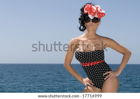 sexy pin up woman near the sea with blue day background and copy space - stock photo