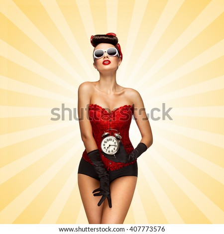 Sexy pinup girl in a red vintage corset holding a retro alarm clock in her hand and posing on colorful abstract cartoon style background.