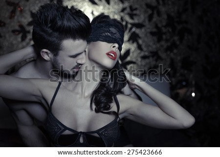 Sexy playful couple in bed, foreplay at night, kissing neck - stock photo
