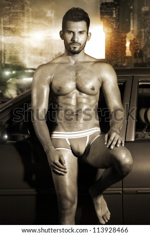 Sexy portrait of a very muscular male model in underwear leaning against car in sensual pose in sepia tones with cool grunge city background - stock photo