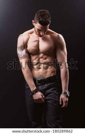 Sexy portrait of a very muscular shirtless male model against black wall in sensual pose - stock photo