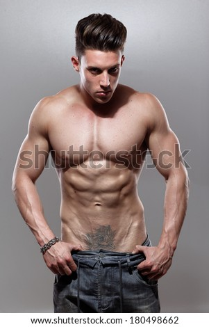 Sexy portrait of a very muscular shirtless male model against grey wall in sensual pose .