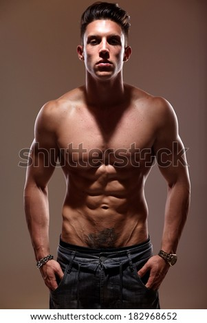Sexy portrait of a very muscular shirtless male model against grey wall in sensual pose .Low light. Shallow depth of field with focus on abdominals.  - stock photo