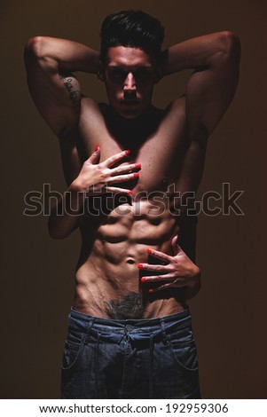 Sexy portrait of a very muscular shirtless male model against grey wall in sensual pose with hands girl on abdomen. Fashion colors. Low light.  - stock photo