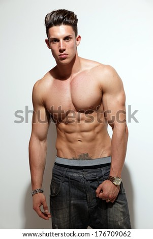 Sexy portrait of a very muscular shirtless male model against white wall in sensual pose . Fashion colors.  - stock photo