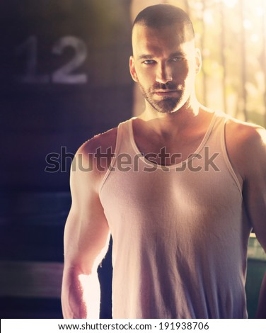 Sexy portrait of masculine man with shaved head in hard dramatic light and shadow - stock photo