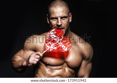 Sexy portrait of romantic man with valentine's lollipop. - stock photo
