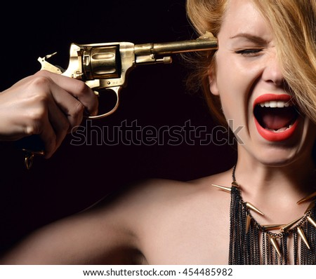 Sexy red hair woman with a gun scream yelling shouting. Beautiful Girl portrait aim gold expensive revolver to her head want to kill herself sign on dark background - stock photo