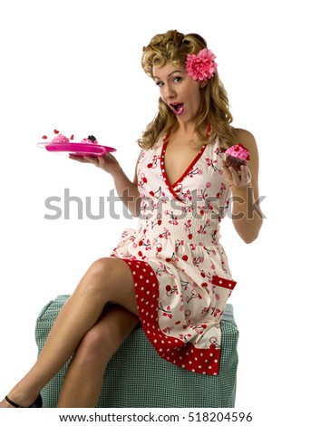 Sexy retro woman in pink dress with flower in her hair showing the sexuality of a housewife.  Shot in studio again a white background