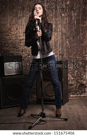 Sexy rock babe in leather jacket singing into a microphone