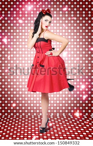 Sexy 80s style woman with pinup haircut and retro polka dot dress disco dancing on a nightclub dance floor  - stock photo