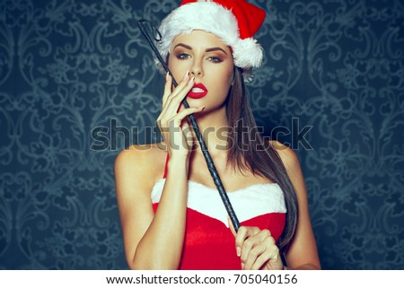 Sexy santa dominatrix woman posing with whip on vintage background