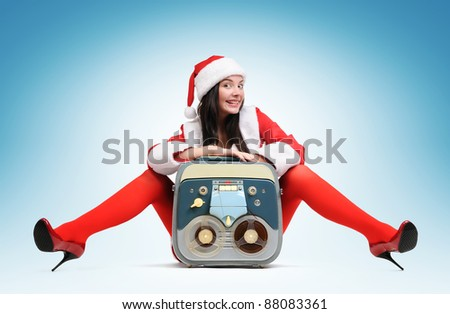 Sexy Santa girl with vintage tape recorder - stock photo