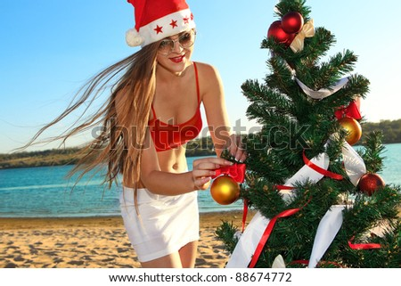 Sexy Santa's helper decking the Christmas tree at the tropical beach - stock photo