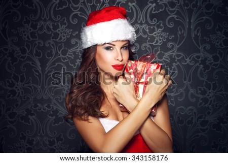 Sexy santa woman embrace christmas gift at vintage wall - stock photo
